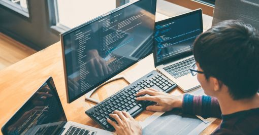 Man coding on three monitors