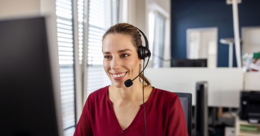 Woman on headset working on computer