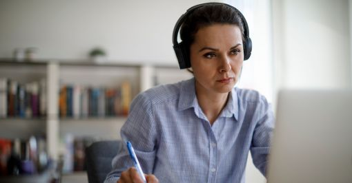 Woman in headphones working on computer