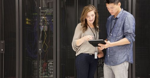 Woman and man looking at tablet in server room