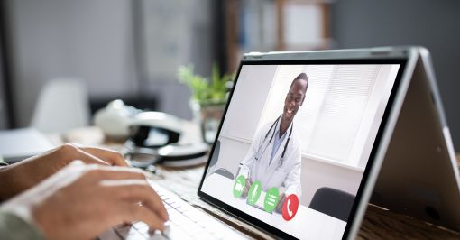 Male doctor video chatting on laptop