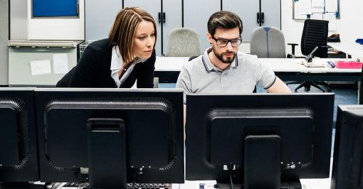 Two people at computer monitors.