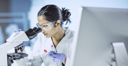 A lab technician looking into a microscope